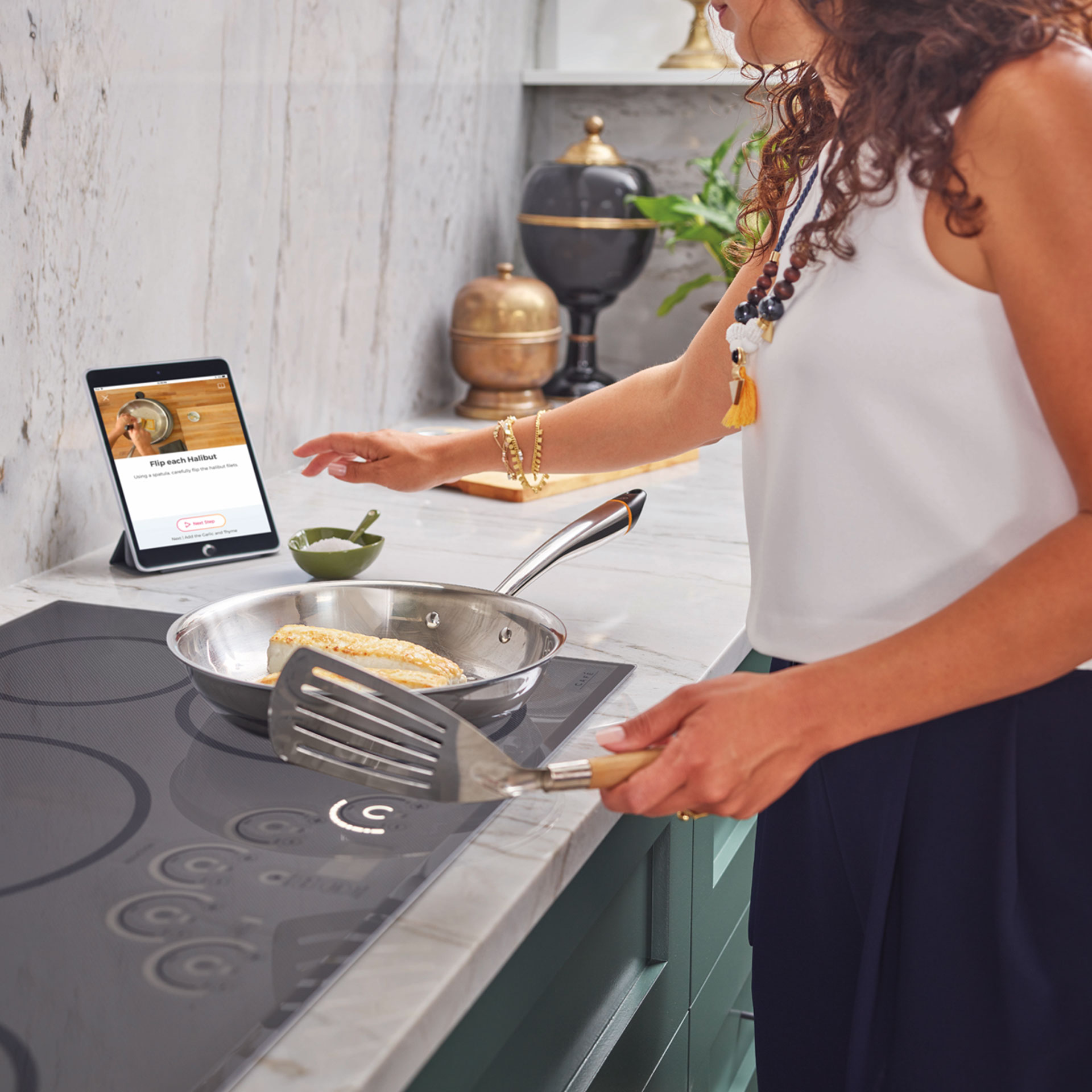woman cooking on induction cooktop using Hestan Cue
