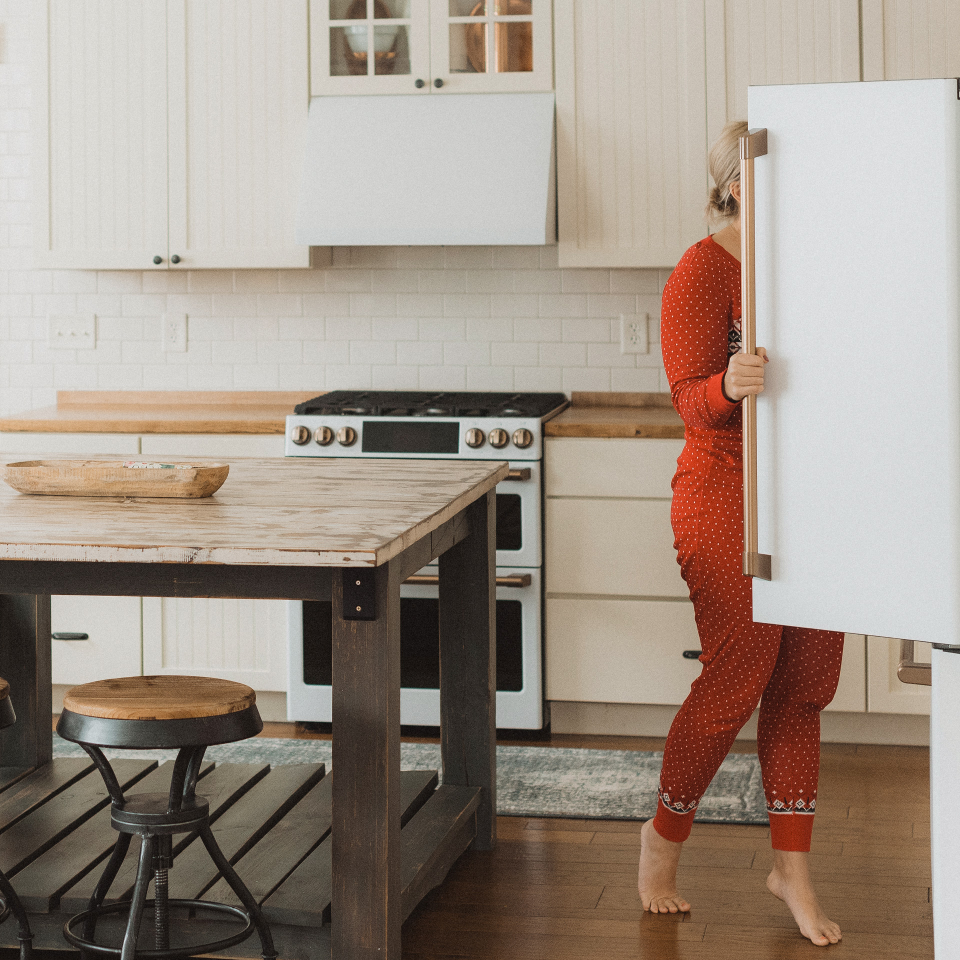 Woman looking in matte white refrigerator