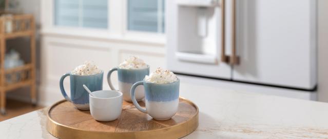 three mugs of hot cocoa with whip cream