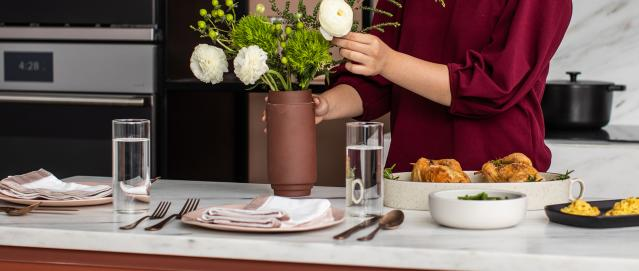 Adjusting Flowers on a Thanksgiving Table Set for Two in Touch of Modern Kitchen