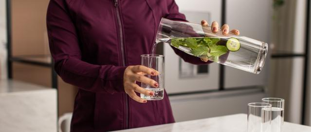 Woman pouring mint-infused water into a glass in front of Modern Glass refrigerator