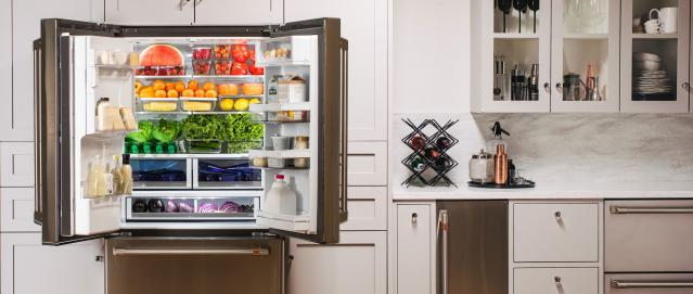 Refrigerator with doors open and a rainbow of groceries inside