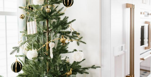 Christmas tree by refrigerator with gold accents