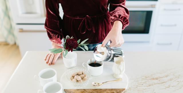 Making coffee in matte white kitchen