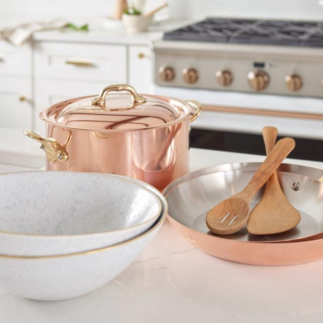 copper cookware with brushed bronze and stainless range