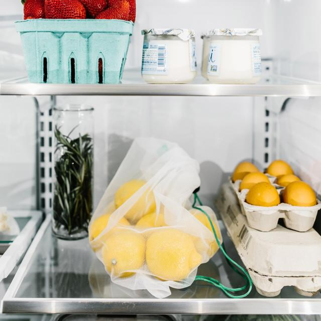 reusable product bags and glass food containers in refrigerator