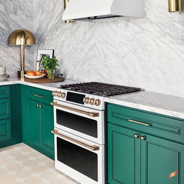 Gas matte white range in kitchen with bright green cabinets