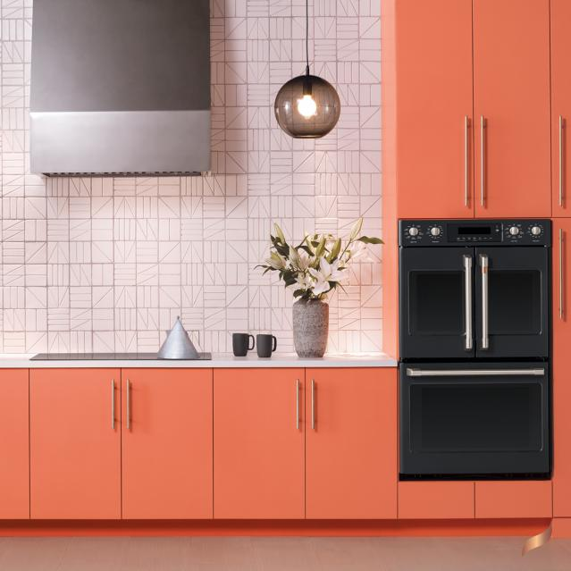 Matte black double wall oven in kitchen with peach cabinets