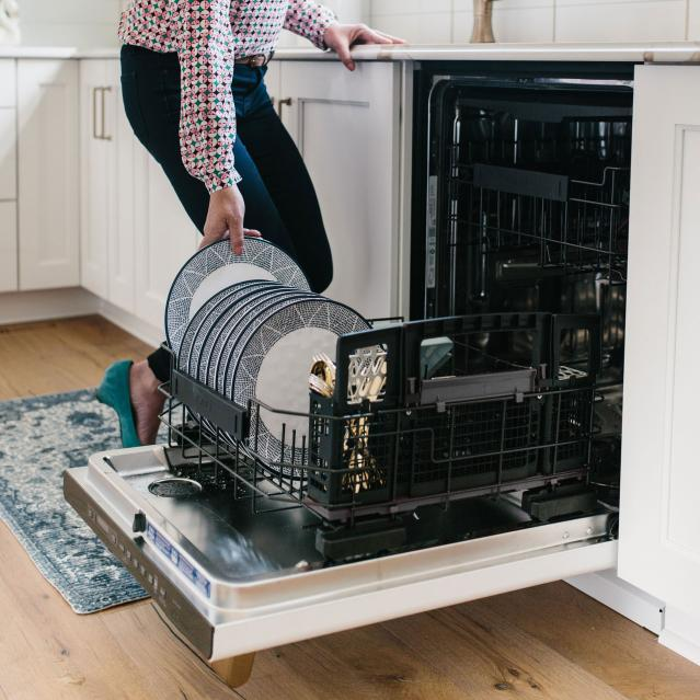Woman taking clean plate out of dishwasher