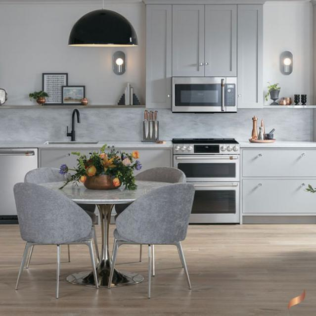 Stainless appliances in contemporary kitchen with light grey cabinets