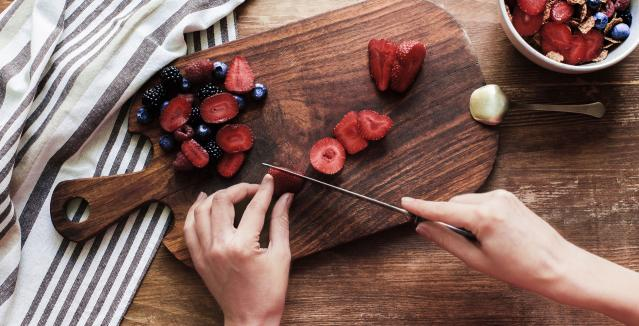 Woman's hands cutting berries on wood cutting board